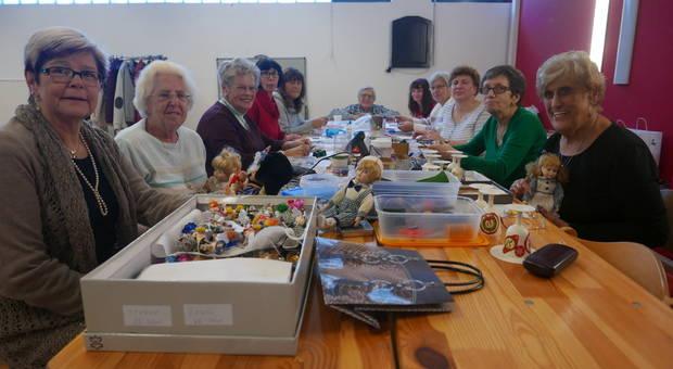 Eine Gruppe von älteren damen an einem Tisch mit Bastelsachen