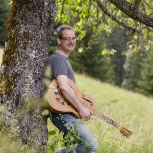 Mann im grauen T-Shirt lehn am Baum und hält seine Gitarre unterm Arm