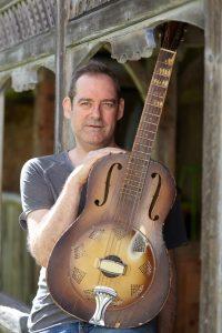 Mann sitzt mit Sener Gitarre im Arm vor einer Hütte