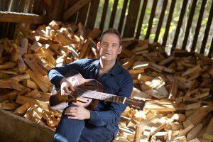 Mann stitzt im blauem Hemd mit seiner Gitarre in der Holzhütte