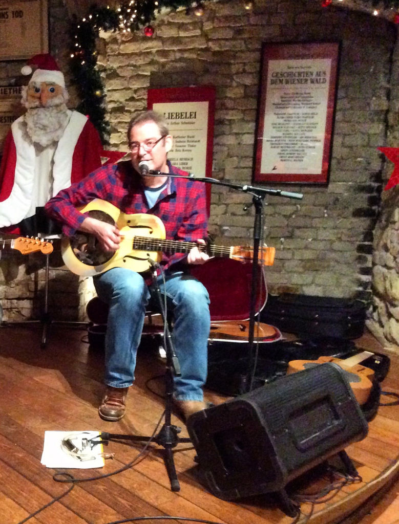 Mann in weihnachtlicher Kulisse singt und spielt Gitarre