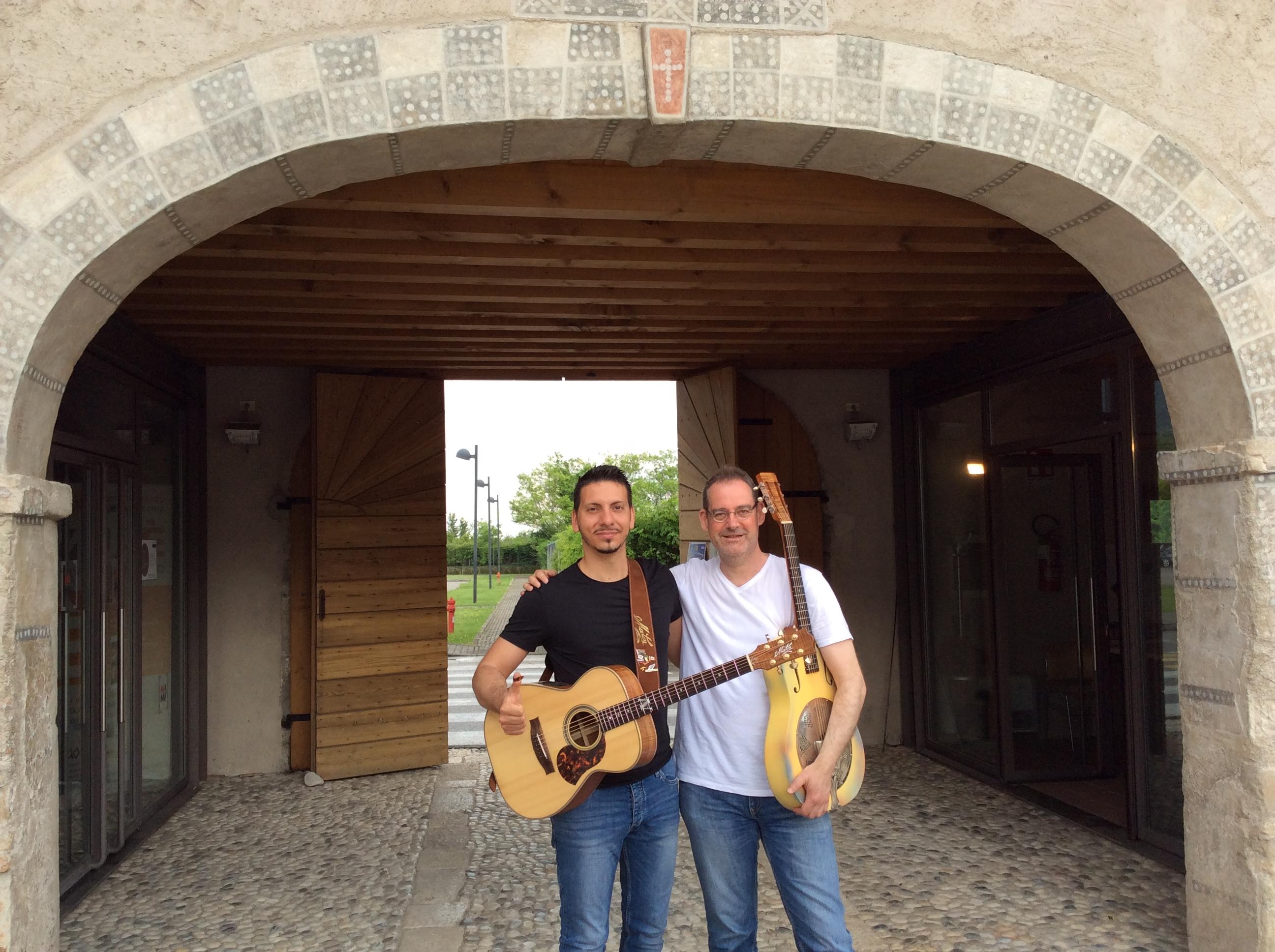 Zwei Männer mit gitarre vor einem großen Haustor